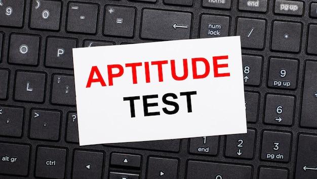黒いコンピューターのキーボードには、aptitudetestというテキストが書かれた白いカードがあります。上から見る