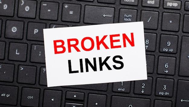 На черной клавиатуре компьютера есть белая карточка с текстом broken links. вид сверху