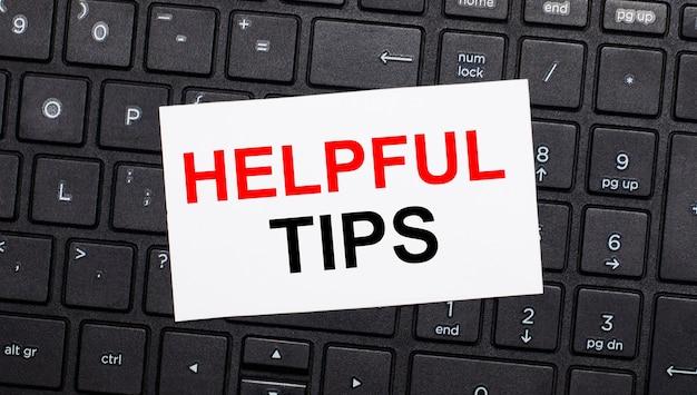 검은 색 컴퓨터 키보드에는 helpful tips라는 텍스트가있는 흰색 카드가 있습니다.