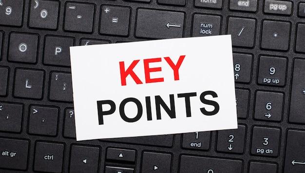 黒いコンピューターのキーボードには、「keypoints」というテキストが付いた白いカードがあります。上から見る