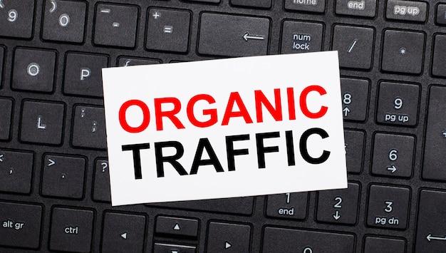 黒いコンピューターのキーボードには、organictrafficというテキストが書かれた白いカードがあります。