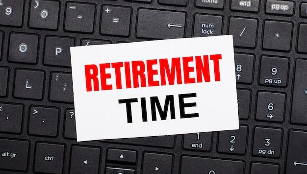 黒いコンピューターのキーボードには、「退職時間」というテキストが書かれた白いカードがあります。