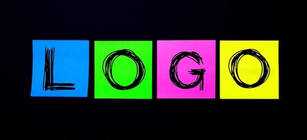 黒い表面に、logoという言葉が書かれた明るい色とりどりのステッカー。図