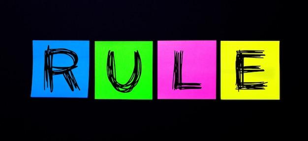 黒い表面に、ruleという言葉が書かれた明るい色とりどりのステッカー