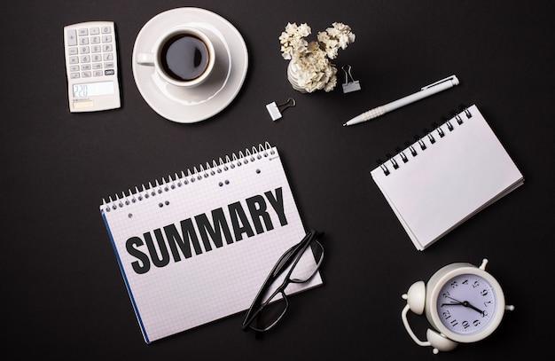 黒い壁に、白い電卓、花、ペン、「summary」と書かれたノート、白い目覚まし時計。ビジネスコンセプト