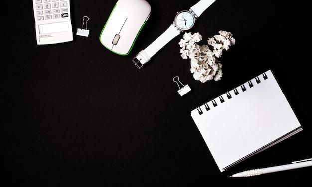 黒い壁に、白い空白のノート、電卓、コンピューターのマウス、花、時計、ペン。コピースペース