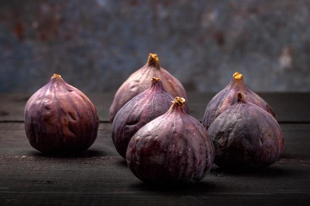 На черном деревянном столе плоды свежего инжира. красивые голубые плоды инжира крупным планом