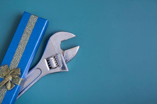 파란색 배경에 렌치가 있는 파란색 선물 상자, 남자, 남자에 대한 선물의 개념. 새해 선물, 생일