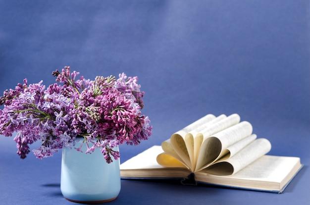 青い背景に小さなセラミックの花瓶にライラックの花束。