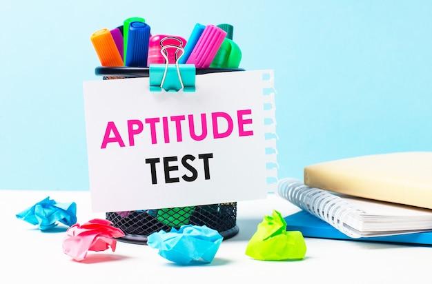 На синем фоне - подставка с яркими маркерами, блокнотами и разноцветными мятыми бумажками. лист бумаги с текстом тест аппитудии.
