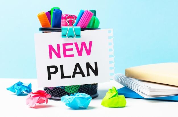 На синем фоне - подставка с яркими маркерами, блокнотами и разноцветными мятыми бумажками. лист бумаги с текстом новый план.