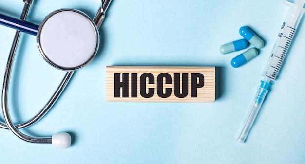 青い背景に、聴診器、注射器、丸薬、hiccupという言葉が書かれた木製のブロック。