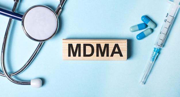 На синем фоне стетоскоп, шприц, таблетки и деревянный брусок с надписью mdma. медицинская концепция