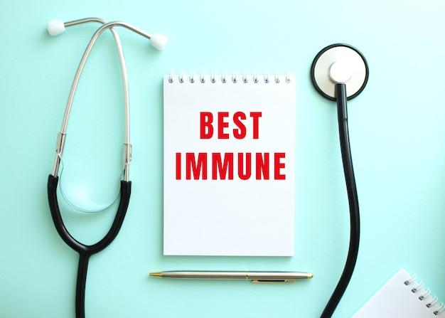 파란색 배경에 청진기 및 빨간색 단어 best immune이 있는 흰색 메모장.