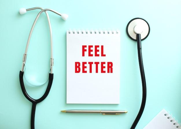 青い背景に、聴診器と赤い言葉が付いた白いメモ帳feel better