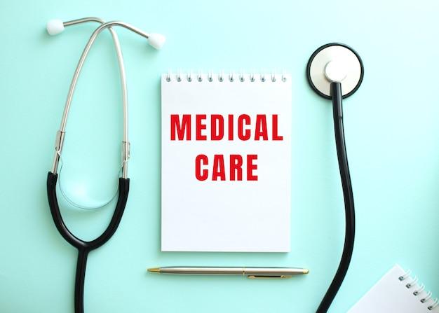 파란색 배경에는 청진기와 빨간색 medical care라는 단어가 있는 흰색 메모장이 있습니다.