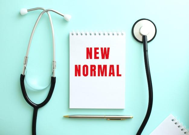파란색 배경에 청진기 및 빨간색 단어 new normal이 있는 흰색 메모장. 의료 개념