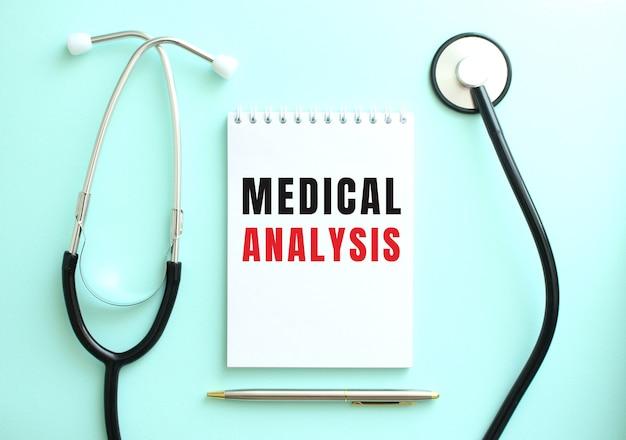 파란색 배경에 청진기와 의료 분석이라는 단어가 있는 흰색 메모장