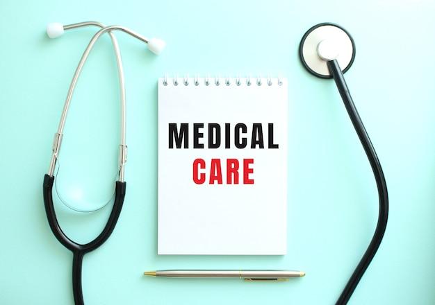 파란색 배경에 청진기와 medical care라는 단어가 있는 흰색 메모장.