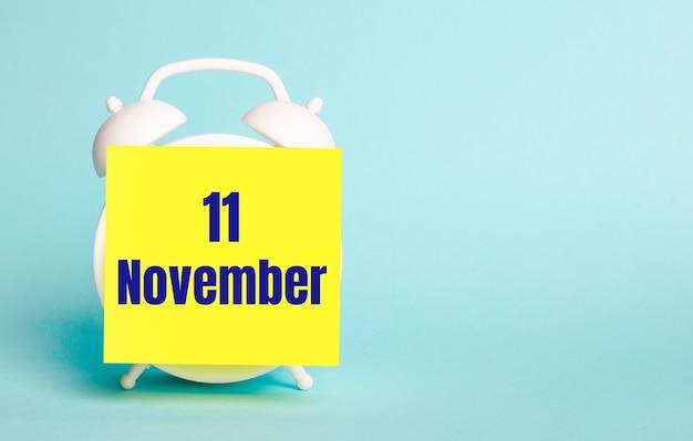 На синем фоне - белый будильник с желтой наклейкой для заметок с текстом 11 ноября.
