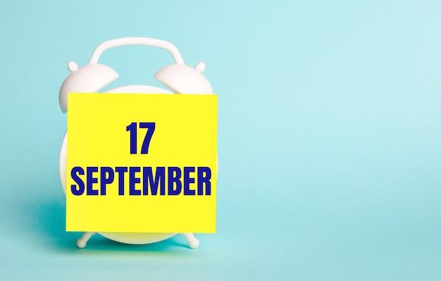 青い背景に-9月17日というテキストのメモ用の黄色のステッカーが付いた白い目覚まし時計。