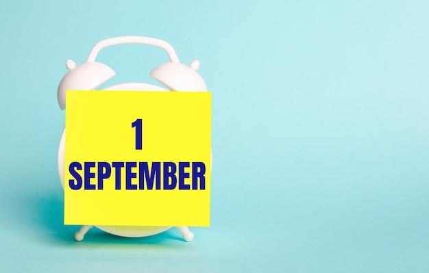 青い背景に-9月1日というテキストのメモ用の黄色のステッカーが付いた白い目覚まし時計。