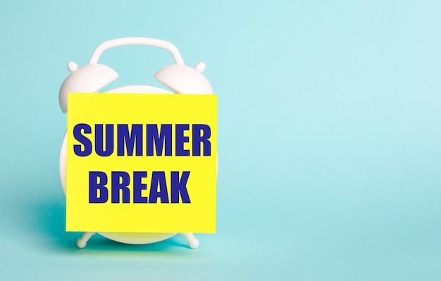 青い背景に-「夏休み」というテキストのメモ用の黄色のステッカーが付いた白い目覚まし時計。