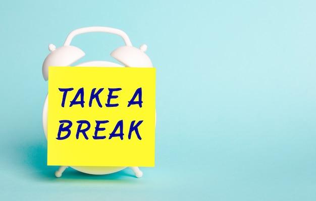 На синем фоне - белый будильник с желтой наклейкой для заметок с текстом take a break.