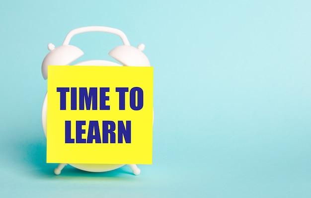 青い背景に-「学習する時間」というテキストのメモ用の黄色のステッカーが付いた白い目覚まし時計。