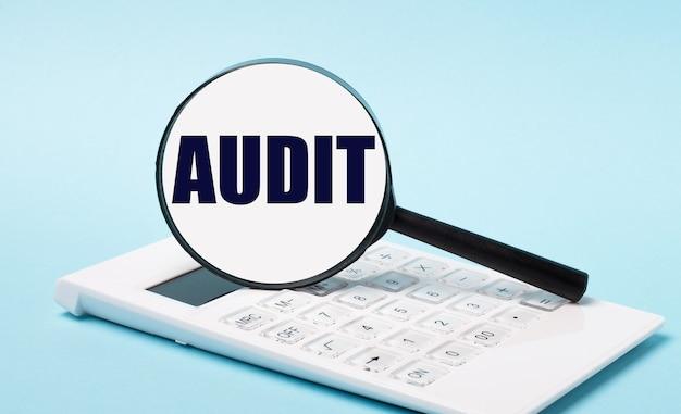 На синем фоне белый калькулятор и увеличительное стекло с текстом audit. бизнес-концепция