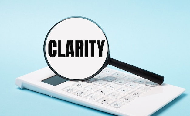 На синем фоне белый калькулятор и увеличительное стекло с текстом ясность. бизнес-концепция