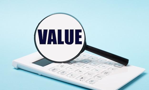 На синем фоне белый калькулятор и увеличительное стекло с текстом value. бизнес-концепция