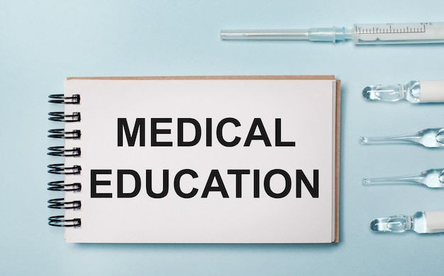 青い背景に薬が入ったアンプルと「医学教育」というテキストが書かれたノート。医療コンセプト