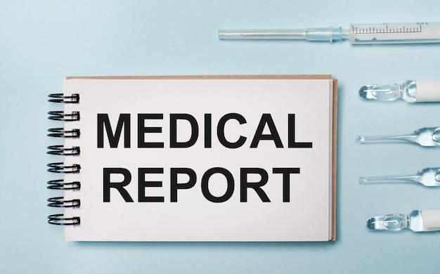 青い背景に薬が入ったアンプルと「medicalreport」というテキストが書かれたノート。医療コンセプト