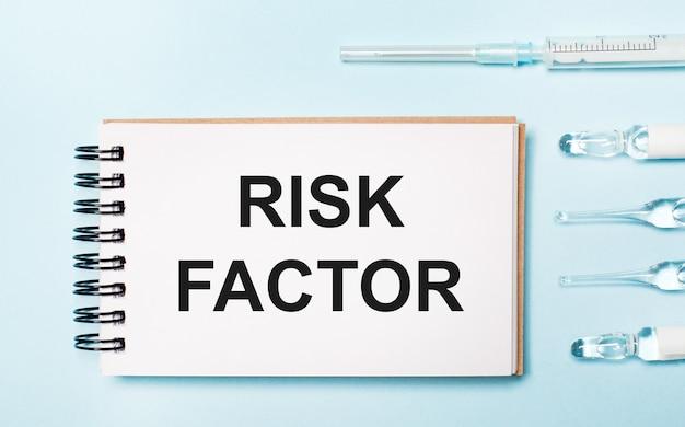 На синем фоне ампула с лекарствами и блокнот с текстом фактор риска. медицинская концепция
