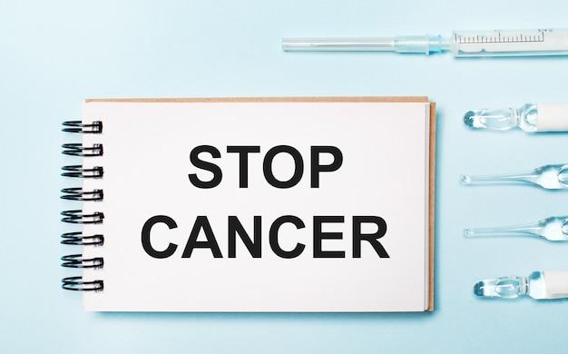 青い背景に薬が入ったアンプルと「stopcancer」というテキストが書かれたノート。医療の概念