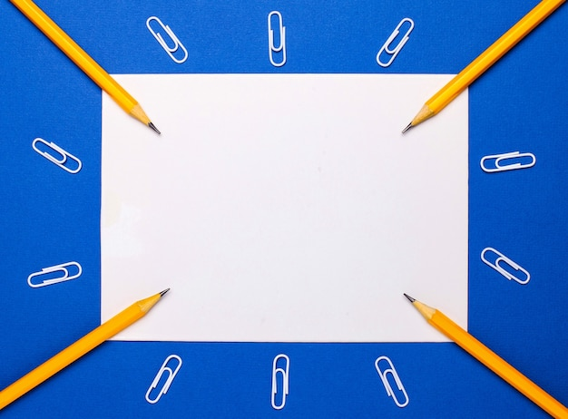 青い背景には、鉛筆とテキストを挿入するスペースのある白い紙があります。レンプレート