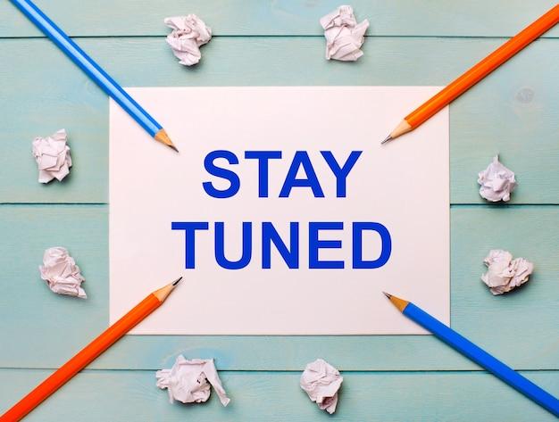 青い背景に-黒とオレンジの鉛筆、白いしわくちゃの紙、白い紙に「staytuned」というテキストが表示されます