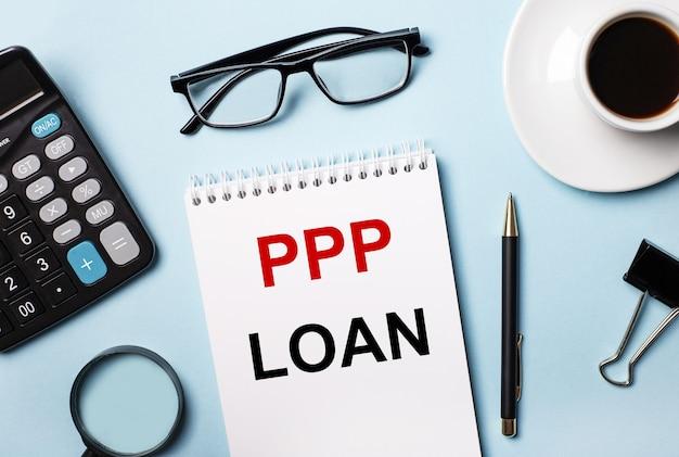 На синем фоне очки, калькулятор, кофе, лупа, ручка и блокнот с текстом ppp loan.