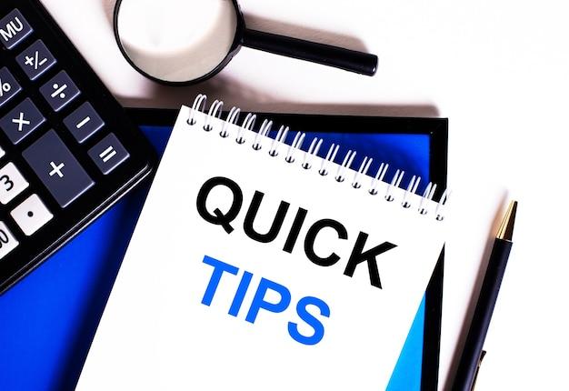 青い背景、電卓の近く、虫眼鏡とペン、「quicktips」と書かれたノート