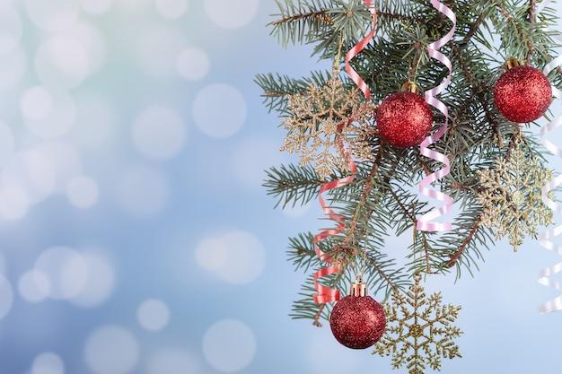 На синем фоне еловая ветка с елочными шарами и новогодней мишурой