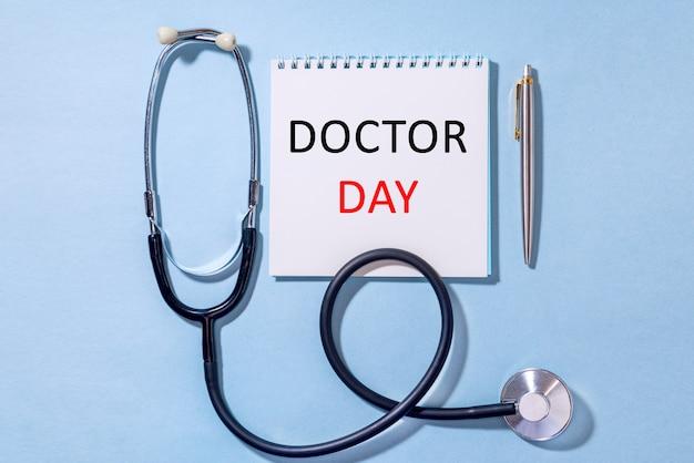 На синем фоне стетоскоп с блокнотом и ручкой текст doctor day