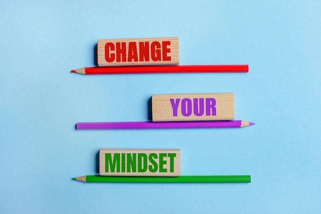 青い背景に、3つの色鉛筆、テキスト付きの3つの木製ブロックあなたの考え方を変えてください