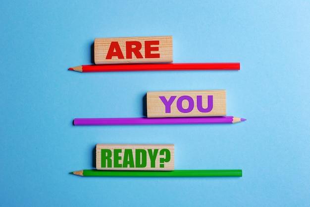青い背景に、3つの色鉛筆、テキスト付きの3つの木製ブロック質問は準備ができていますか