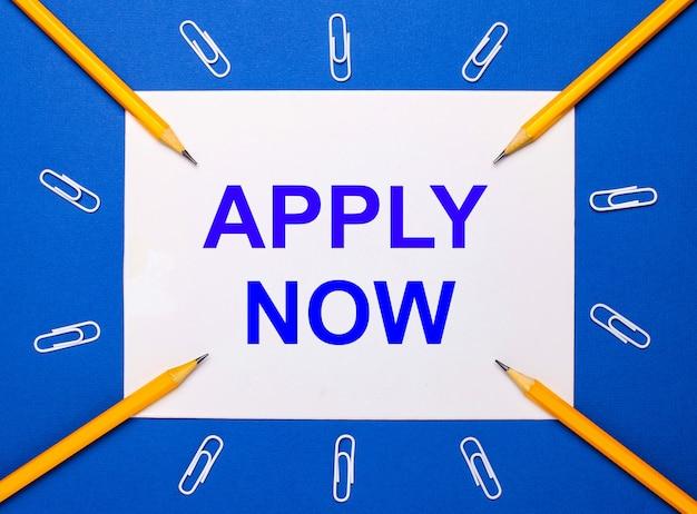青い背景に、白いペーパークリップ、黄色の鉛筆、白い紙に「今すぐ申し込む」というテキストが表示されます