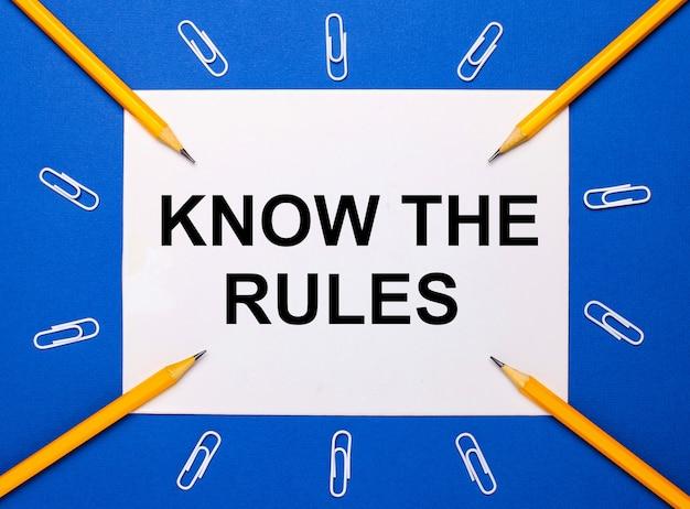 На синем фоне белые скрепки, желтые карандаши и белый лист бумаги с текстом знай правила.