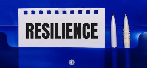 На синем фоне белые ручки и лист бумаги с надписью resilience.