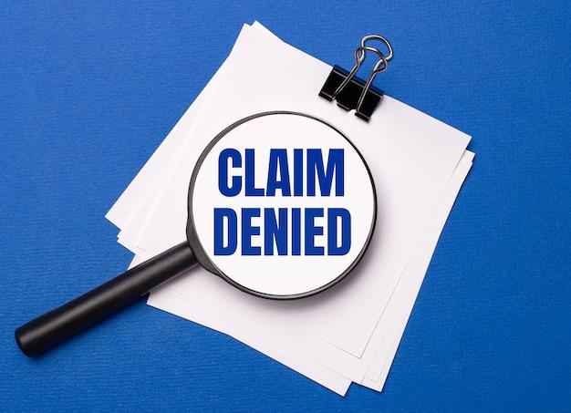 파란색 배경에 검정색 종이 클립 아래에 있는 흰색 시트와 그 위에 claim denied라는 텍스트가 있는 돋보기가 있습니다.
