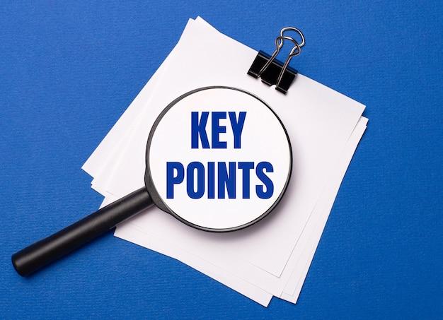 На синем фоне белые листы под черной канцелярской скрепкой и на них увеличительное стекло с текстом ключевые моменты