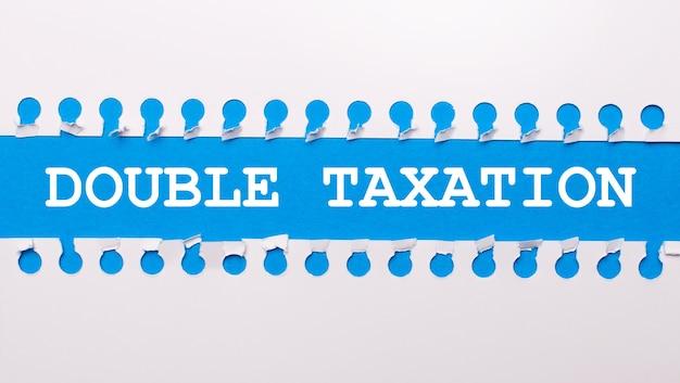 На синем фоне с текстом двойное налогообложение две белые рваные полоски бумаги.